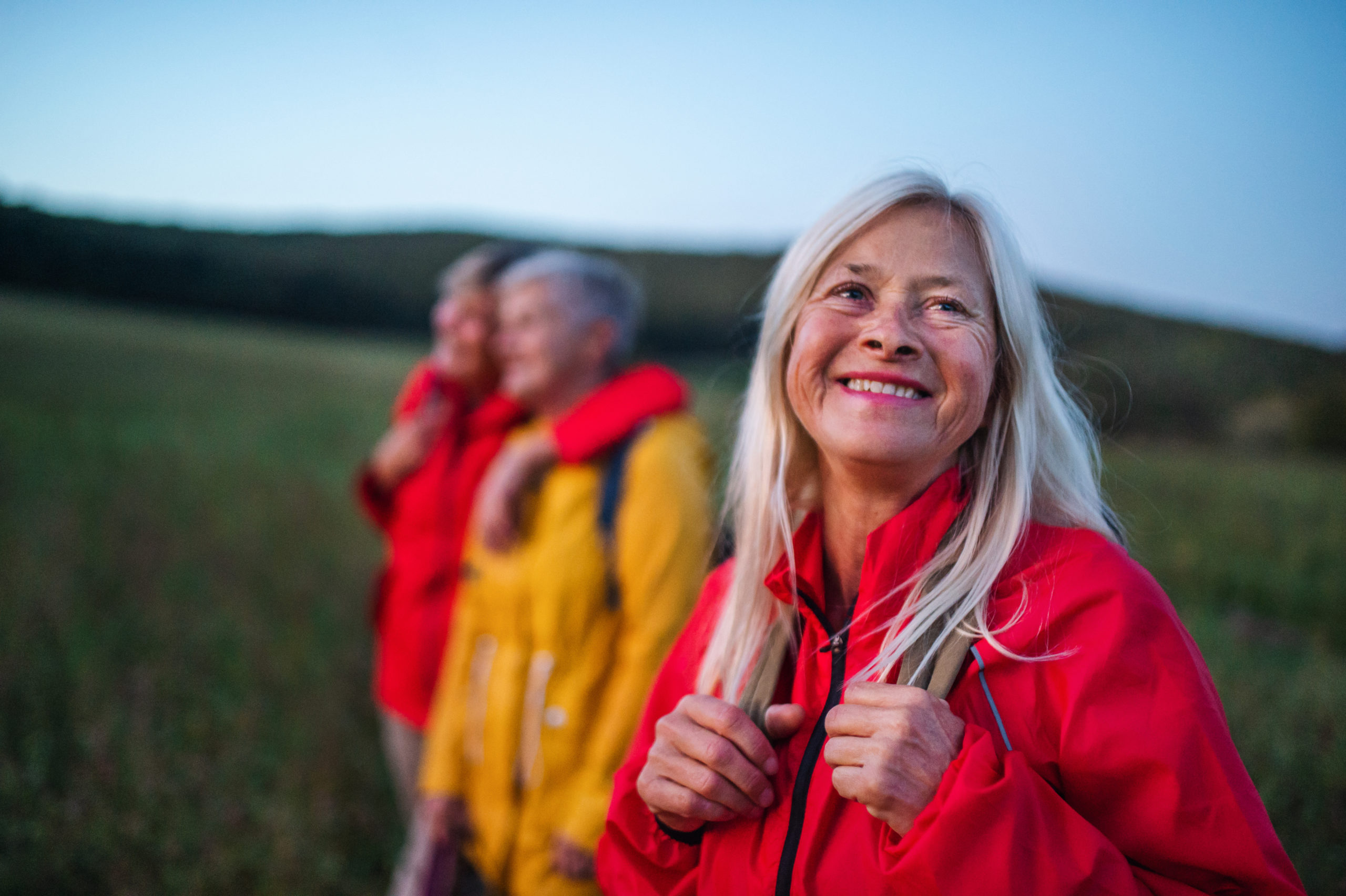 Senior Women Friends On Walk Outdoors In Nature At Dusk.